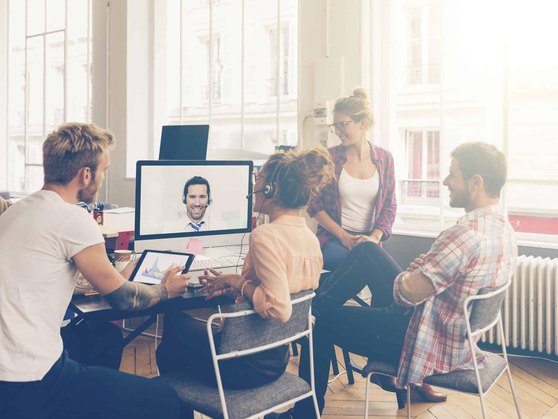 Ein Monitor und vier Personen die davor sitzen