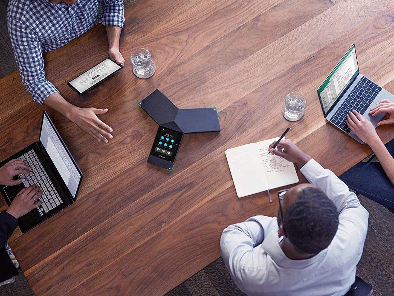 Vier Personen an einem Tisch in einer Sitzung