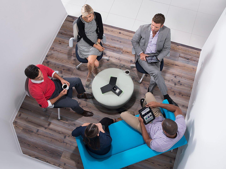 Fünf Personen in einer Sitzung mit einem Telefonkonferenzsystem