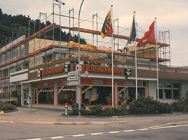 Kilchenmann Geschichte 1989 zeigt Gebäude in Kehrsatz mit Baugerüst