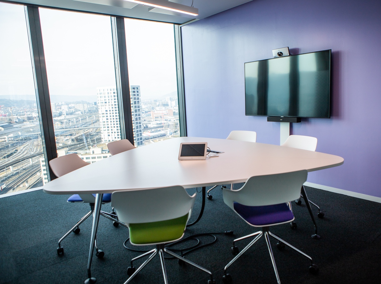 Buntes Sitzungszimmer bei Cognizant mit Displays und 6 Stühlen und einem Tisch