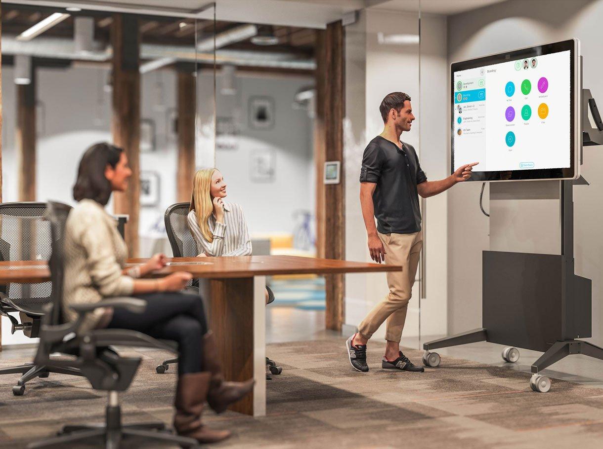 Mann zeigt in einem Sitzungszimmer auf ein Collaboration Board